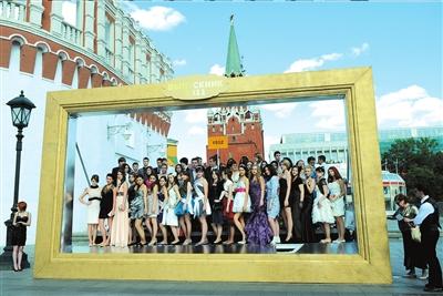 俄罗斯莫斯科克里姆林宫外,一所学校的毕业生站在一个大相框里拍照